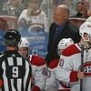 Un entraîneur de hockey derrière le banc de ses joueurs sourit à l'arbitre.