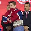 Cole Caufield¸enfile un chandail du Canadien de Montréal.