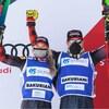 Ils lèvent leurs bras et leurs skis sur le podium.