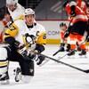 Pendant un échauffement, Crosby est agenouillé. En arrière-plan, des joueurs des Flyers.