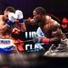 Un boxeur donne un coup au visage d'un adversaire.