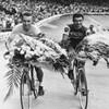 Ils sont sur la piste d'un vélodrome et portent un bouquet de fleurs sur leur guidon.