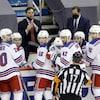 L'entraîneur-chef des Rangers, son masque sur le menton, demande un temps d'arrêt à l'arbitre, sous le regard des joueurs de son équipe et de son adjoint principal.