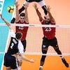Les Canadiens Derek Epp et Danny Demyanenko essaient de bloquer la touche du Polonais Maciej Muzaj à la Coupe du monde de volleyball.