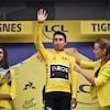 Le coureur salue la foule de la main avec son maillot jaune.