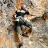 Un homme escalade une paroi de roche.