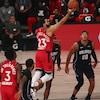 Un joueur de basketball s'élance vers le panier avec le ballon en main.