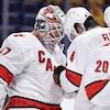 Des joueurs de hockey se félicitent en se cognant la tête après une victoire.
