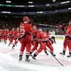 Les joueurs passent sous un bâton de hockey.