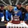Les joueurs de curling prennent la pose devant un trophée.