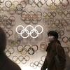 Des visiteurs qui portent des masques se promènent parmi les anneaux olympiques dans le musée olympique de Tokyo.