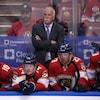 Alors que ses joueurs regardent l'action, assis au banc, l'entraîneur-chef des Panthers, en veston noir, est debout derrière eux, les bras croisés, le regard sévère.