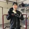 Jeune homme avec casquette, tenant son bâton de hockey.