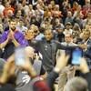 Kawhi Leonard salue la foule alors que ses anciens coéquipiers, rangés derrière lui, l'applaudissent. Les partisans à l'avant-plan tentent de prendre le joueur étoile en photo.