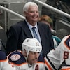 Ken Hitchcock affiche un grand sourire alors qu'il se tient derrière le banc des Oilers durant un match.