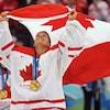 Une gardienne de but au hockey fait flotter le drapeau canadien au-dessus de sa tête. Elle a une médaille d'or autour du cou.