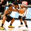Le meneur des Nets Kyrie Irving protège le ballon, tout près de la ligne de trois points, surveillé de près par son vis-à-vis des Raptors.