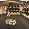 Un plan large d'un vestiaire de hockey vide, avec l'équipement des joueurs dans les casiers