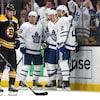 Les joueurs des Maple Leafs de Toronto célèbrent un but devant leur adversaire John Moore.