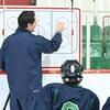 Matthew Lombardi donne des explications au tableau à de jeunes hockeyeurs.