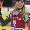 Elle sourit à la caméra, les skis en main.