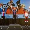 Molly Simpson est sur la troisième marche du podium, les bras dans les airs avec un bouquet dans la main droite et un trophée dans la main gauche.