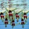 Les athlètes réalisent une figure sous l'eau.
