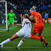 Deux joueuses adverses luttent pour la possession du ballon près de la ligne de fond.