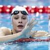 Elle salue de la main droite dans la piscine.