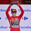 Le cycliste prend la pose en soulevant le trophée du jour.