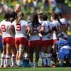 L'entraîneur donne ses instructions aux joueuses rassemblées autour de lui.