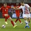 Le milieu de terrain du Canada Samuel Piette contrôle le ballon entre deux joueurs américains lors d'un match de soccer à Toronto.