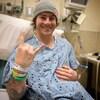 Il est tout sourie sur un lit d'hôpital.