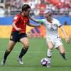 Elle porte sa main au visage d'une adversaire en tentant de maîtriser le ballon.
