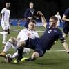 Amar Sejdic (à gauche), de l'Université du Maryland, et Cario Ritaccio, d'Akron), se jettent au sol pour mettre le pied sur le ballon.