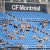 Des amateurs de soccer sont assis dans les gradins.