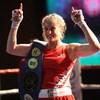 Une boxeuse lève les bras en triomphe avec une ceinture à son épaule.