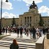 Des centaines de personnes manifestent devant le palais législatif à Regina.