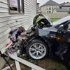 Le devant de la voiture et le mur d'une maison sont lourdement endommagés.