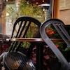 Deux chaises sont accotées sur une table de terrasse.