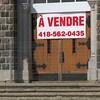 Portes de l'église avec une pancarte À Vendre et un numéro de téléphone.