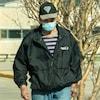 Un homme portant un masque de procédure marche dans la rue.