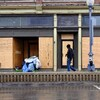 Les effets personnels de personnes sans-abri sont déposées près d'un édifice condamné et barricadé. On voit un passant qui marche devant la bâtisse.