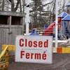 Une affiche temporaire à l'entrée d'un parc de jeux pour enfant indique la fermeture des lieux.