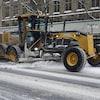 Un immense tracteur jaune sur les rues enneigées du centre-ville d'Ottawa.