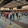Dans une grande salle du palais de congrès, une file de résidents présents pour recevoir leur vaccin.