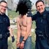 Deux policiers en uniforme sourient autour d'un homme menotté et torse nu. Le visage de l'homme menotté est noirci pour cacher son identité.