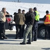 Plusieurs hommes sont regroupés, quelques-uns sont au téléphone, autour de véhicules stationnés.