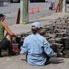 Deux citoyens enlèvent des pavés de béton sur la rue du Roi près d'une borne-fontaine.