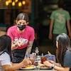 Une serveuse portant le masque discute avec deux clientes.
